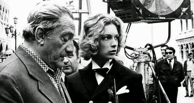 Luchino visconti (left) and Bjorn Andresen (right) appearing together at the Cannes film festival in March 1971, as seen on the black and white photoghraph.