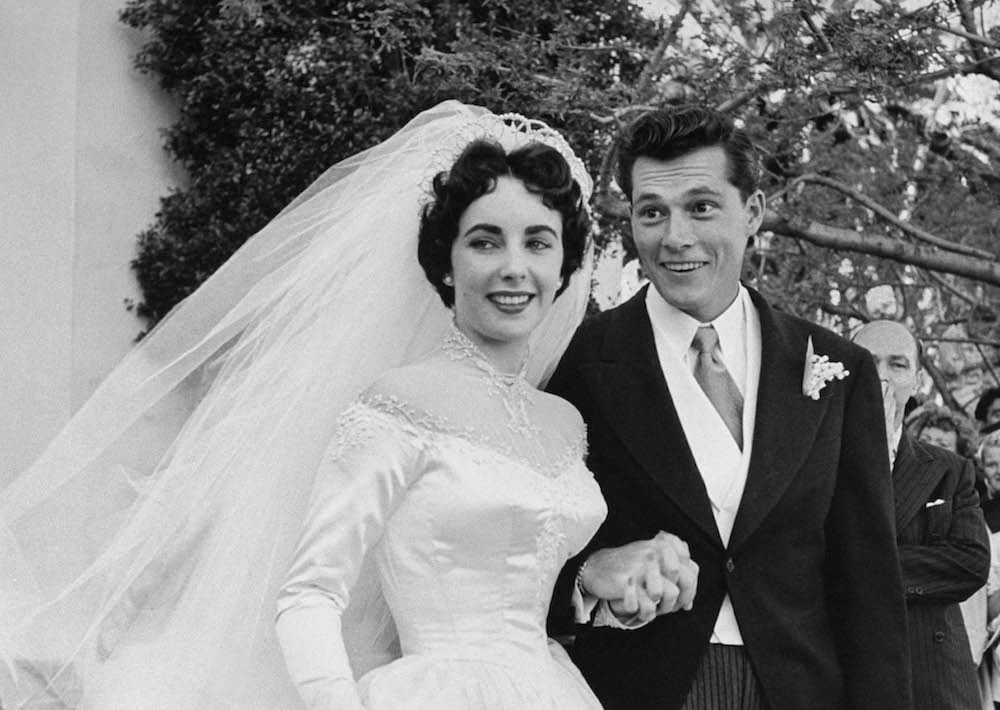 Elizabeth Taylor wearing beautiful satin wedding gown worth $1,500, holding hands with her 1st husband Nicky Hilton after their wedding