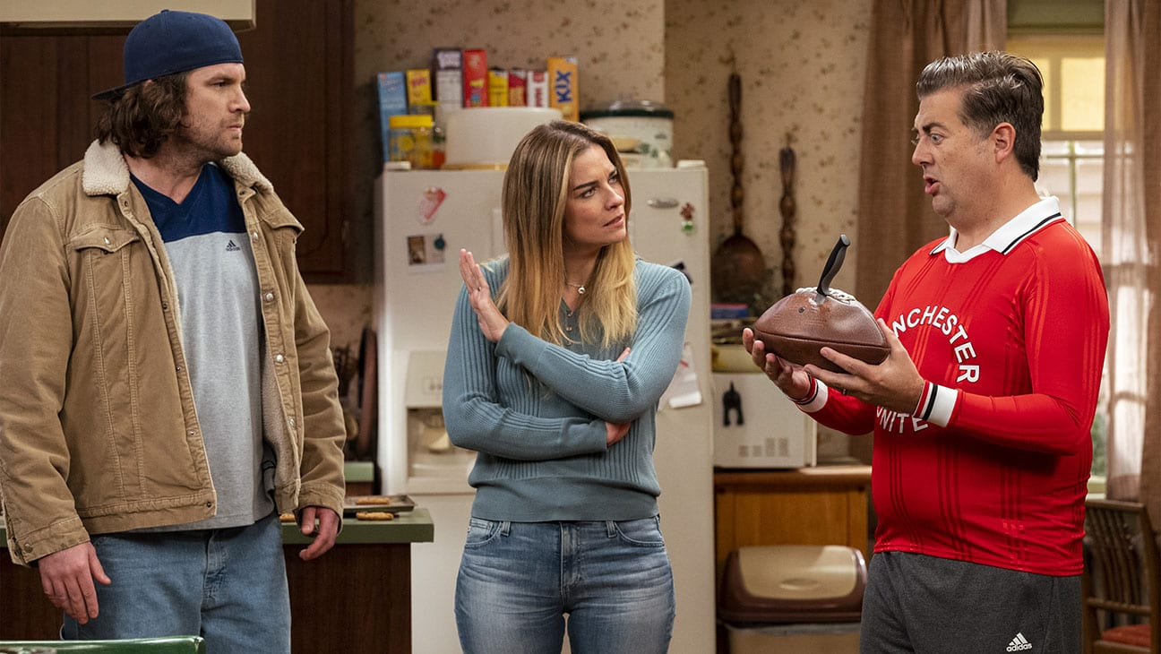 Allison stands in her kitchen between her husband Kevin (right) and his friend (left). Her hand is raised to silence the latter as Kevin shows her an American football with a knife sticking out of it.